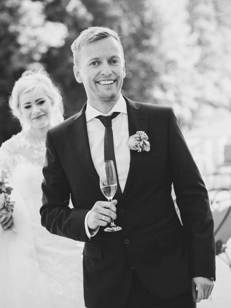 Groom and Bride smiling with Champagne flute Kokkedal Slot Copenhagen