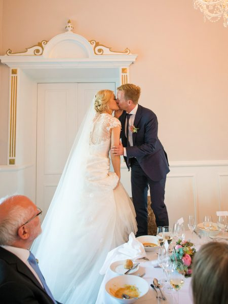 Bride and Groom kiss standing on chairs for the Scandinavian tradition during wedding breakfast