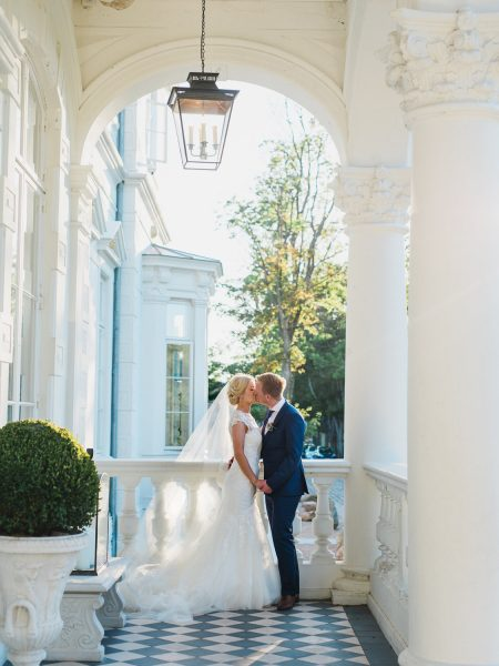 Fine art portrait of Bride and Groom kissing in elegant porch of Kokkedal Slot Copenhagen