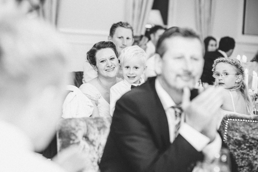 Page boy on mother's lap smiling during a speech at Emotional bride during Groom's speech at Kokkedal Slot Copenhagen