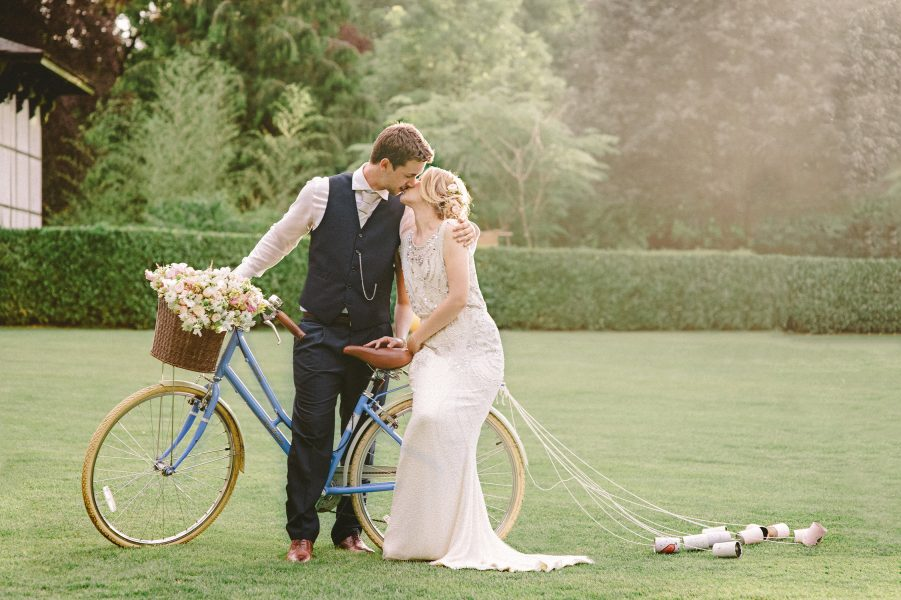Bride and Groom rest on vintage blue bike with flowers and exchange a kiss on the lawn at Larmer Tree Gardens Wiltshire