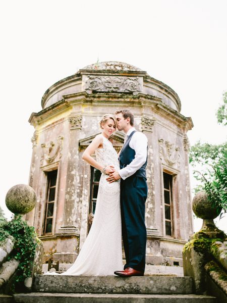 Fine Art Portrait of Bride beaded Jenny Packham dress and Groom in navy suit stand front of the temple of Larmer Tree Gardens Wiltshire