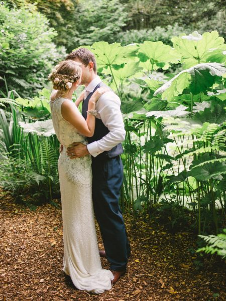 Bride and Groom dance and kiss in a magical secret garden within the grounds of Larmer Tree Gardens Wiltshire