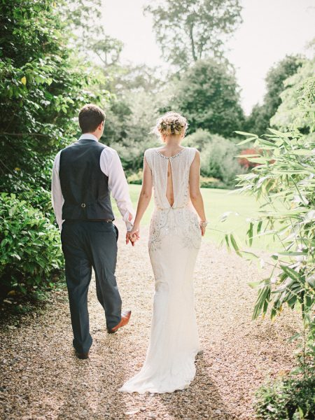 Bride and Groom walk away from camera into beautiful sunlight in the grounds of Larmer Tree Gardens Wiltshire