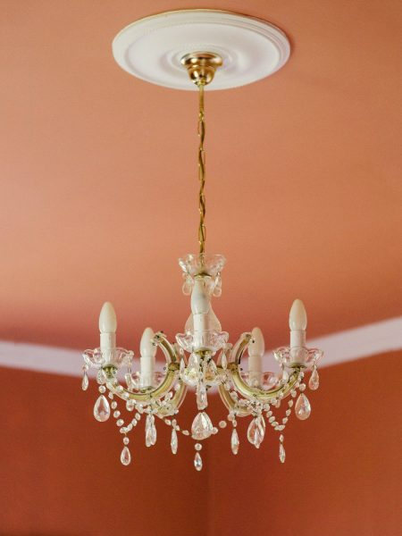 Chandelier with burnt orange wall and ceiling