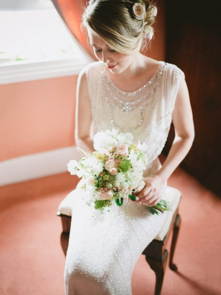 Fine Art Portrait of Bride with blush roses in her hair in fresh make up and sequinned Jenny Packham Dress looks at her blush sweet pea and rose bouquet on her wedding day in Wiltshire