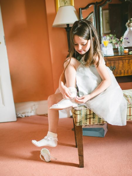 Flower girl sitting on chair tying up shoes Wilshire wedding day