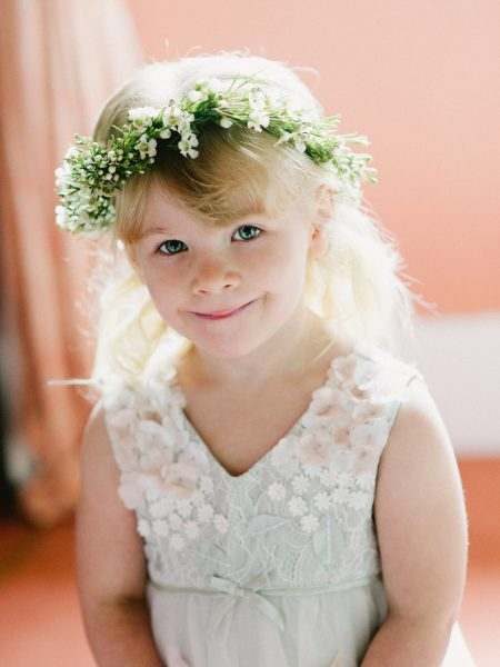 Flower girl with floral crown smiles at camera on a Wiltshire wedding day