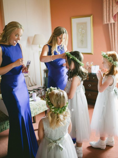Bridesmaids in peacock blue purple dresses excitedly help put floral crowns on Flower girls in a Wiltshire wedding day