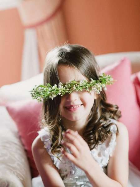 Flower girl with floral crown covering her eyes in a comedy moment on a Wiltshire wedding day