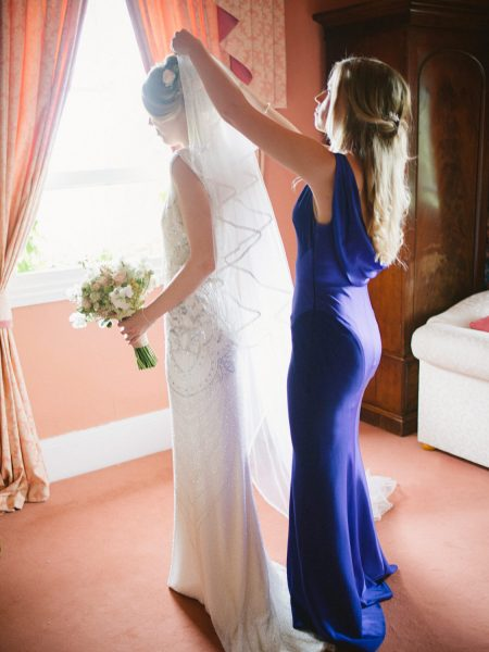 Maid of Honour putting veil on Bride in Jenny Packham beaded dress in a window in a Wiltshire wedding day
