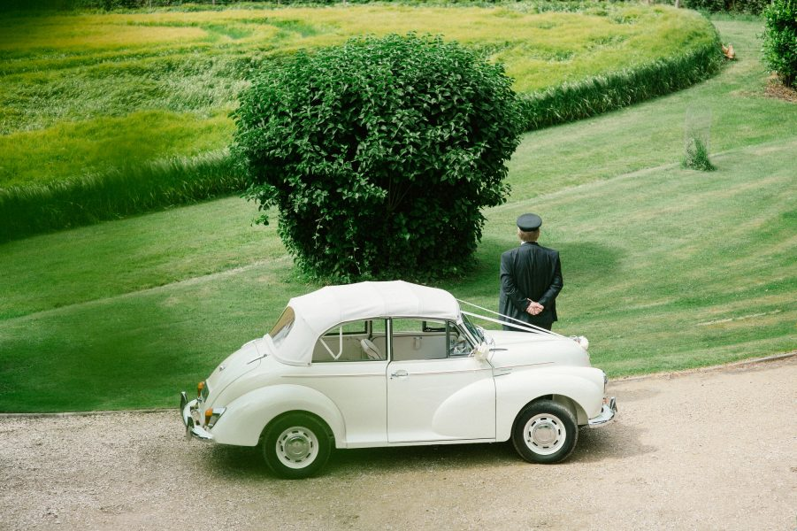 White Morris Minor with driver looking into meadow on a Wiltshire wedding day