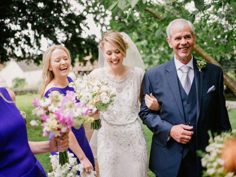 Bride, Father and Bridesmaids arrive at the church with big smiles on their faces