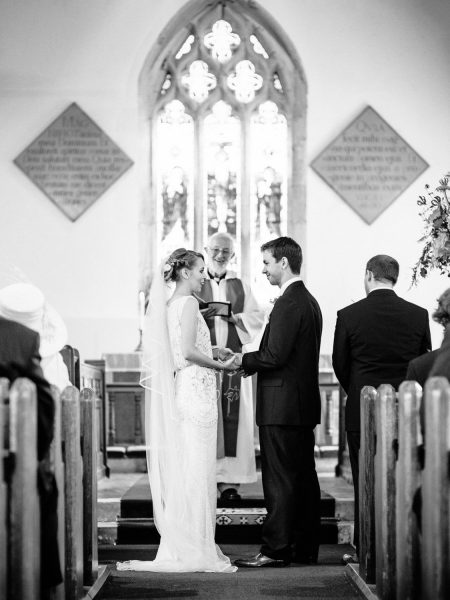 Wedding ceremony full length Bride and Groom taking vows with church window in background