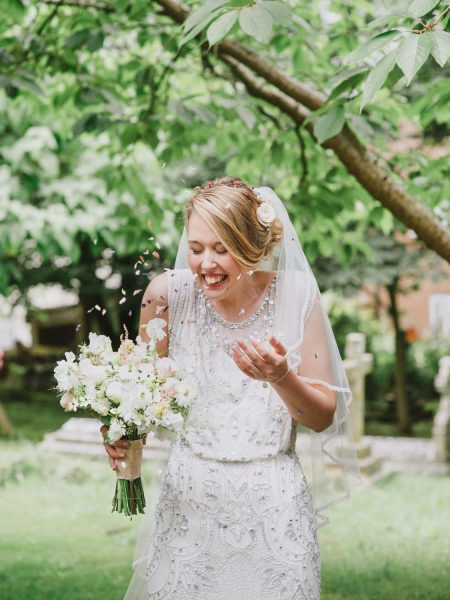 Bride laughing as she throws confetti over herself outside the church