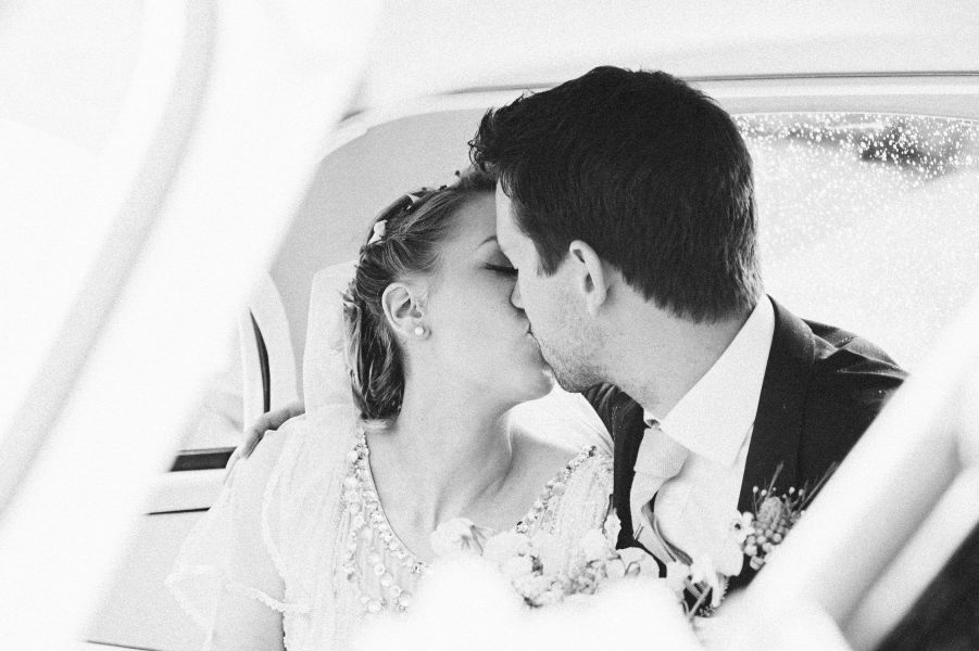 Bride and Groom kiss in back of Morris Minor wedding car Wiltshire wedding