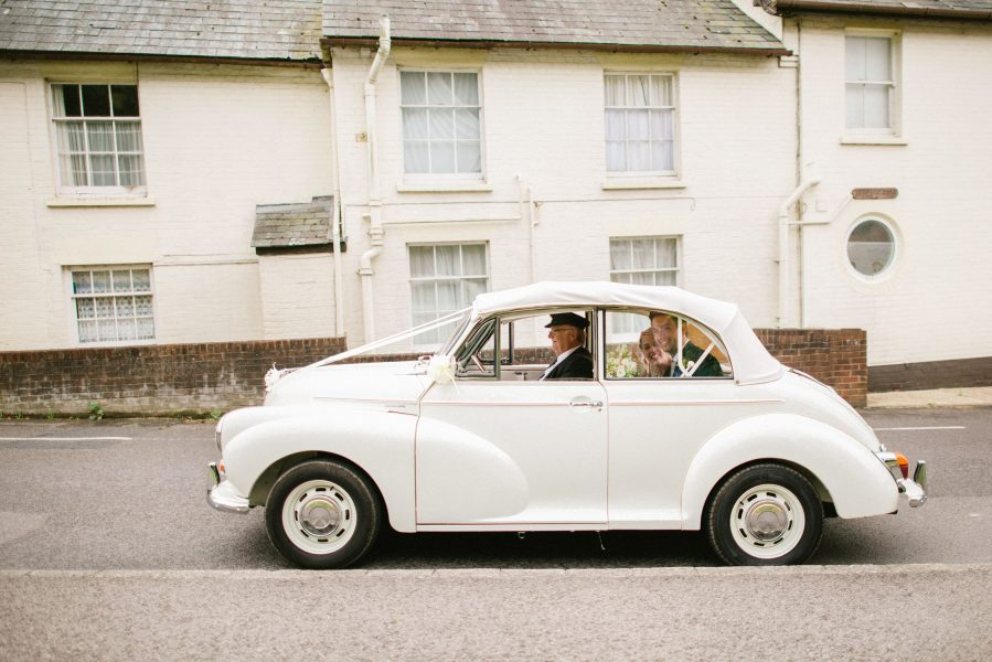 Bride and Groom drive off in White Morris Minor from church to Larmer Tree Gardens