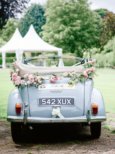 Fine Art Portrait convertible powder blue Morris Minor with pink floral decoration on the lawn at Larmer Tree Gardens