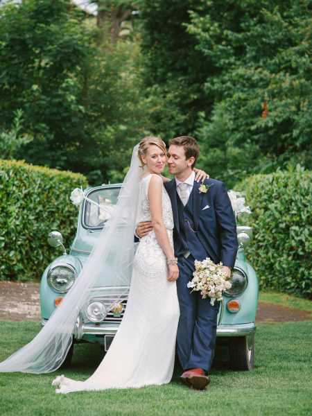 Bride and Groom kiss in front of pastel blue Morris Minor wedding car
