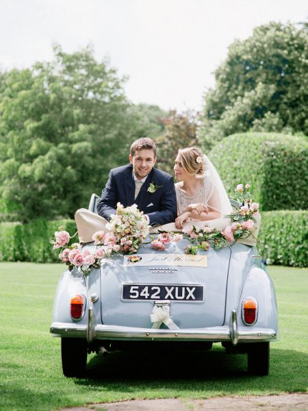 Bride and Groom lean over the back of a pastel blue Morris Minor wedding car