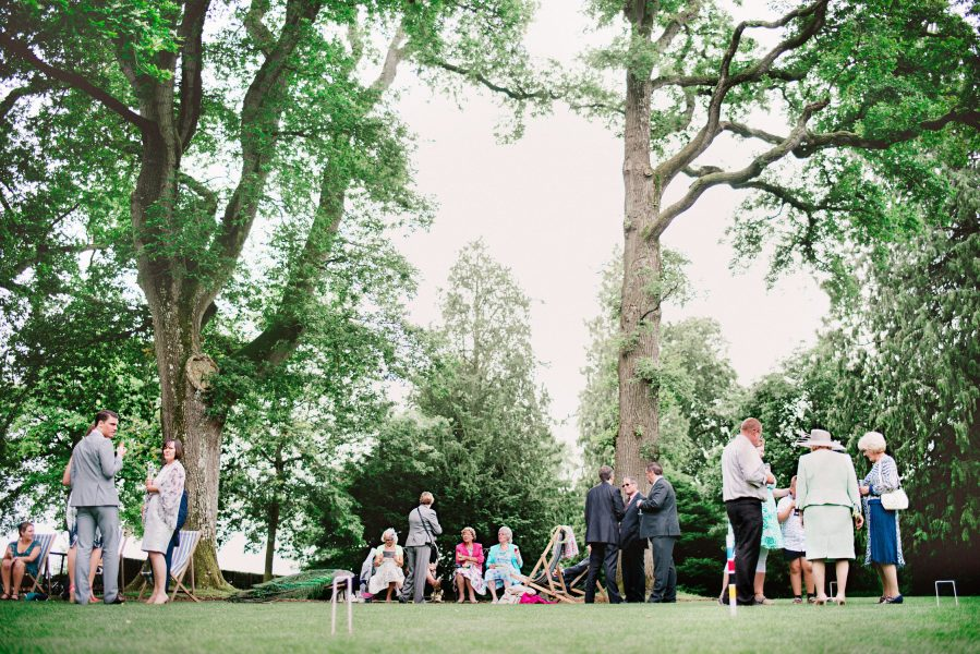 Wide shot of tall trees, wedding guests enjoying the reception sitting in deck chairs with croquet hoops in foreground Larmer Tree Gardens Wiltshire