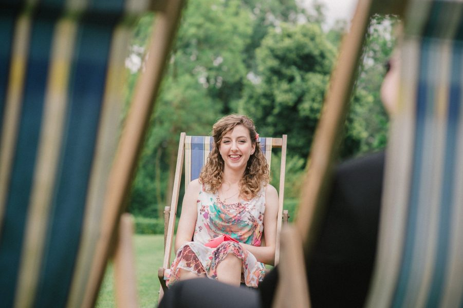 Wedding guest in a deck chair framed by deck chairs Larmer Tree gardens Wiltshire