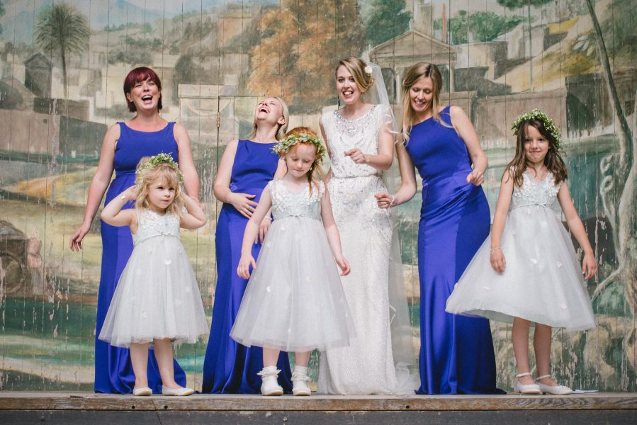 Group Portrait of Bride, Bridesmaids and flower girls having a fun portrait on stage Singing Theatre Larmer tree Gardens Wiltshire