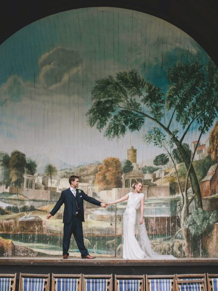 Bride and Groom full length fun dancing portrait on stage Singing Theatre Larmer tree Gardens Wiltshire