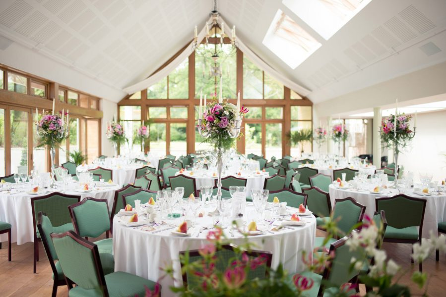Wide shot of whole wedding breakfast decorated room table setting Larmer Tree Gardens