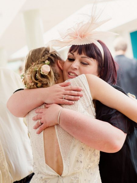 Bride and guest hugging