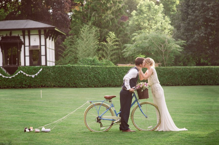 Fine Art Portrait of Bride in Jenny Packham beaded dress kissing Groom who is riding a vintage bike within the grounds of Larmer Tree Gardens Wiltshire