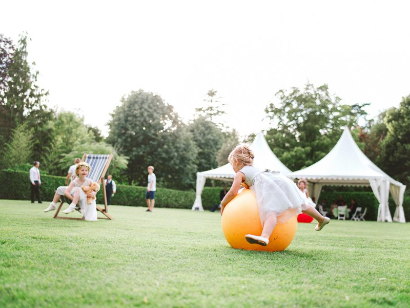 Candid landscape scene of flower girl playing on space hopper at Larmer Tree Gardens Wiltshire