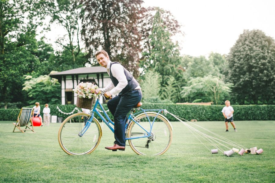 Groom cycling blue vintage bike with tin cans trailing from back in grounds of Larmer Tree Gardens Wiltshire