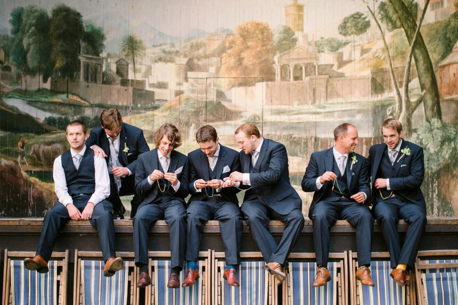 Groom, Best Man and Ushers sit on stage of Singing Theatre playing with their pocket watches at Larmer Tree Gardens Wiltshire