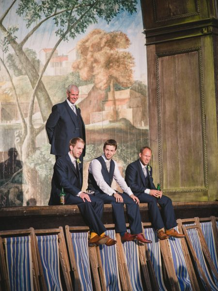Groom, Father and brother sit on stage of Singing Theatre at Larmer Tree Gardens Wiltshire