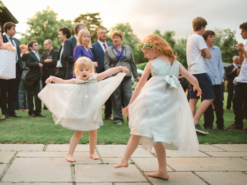 Flower girls play and dance in pretty soft green dresses as the sun sets at Larmer Tree Gardens Wiltshire