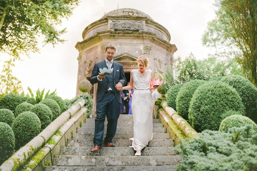 Bride and Groom walk down stone staircase carrying flower lanterns with red temple in background Larmer Tree Gardens Wiltshire