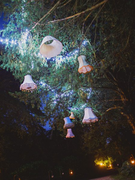 Quirky lampshades hanging in trees providing unusual decoration Larmer Tree Gardens Wiltshire