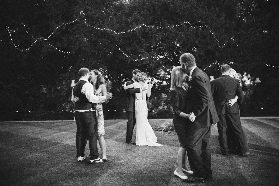 Bride and Groom dancing outside with guests and string lighting in trees Larmer Tree Gardens Wiltshire