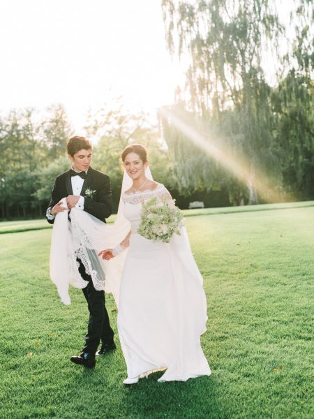 Black tie stylish Bride and Groom natural portrait back lit by sunshine walking happily on lawn at Sølyst Copenhagen