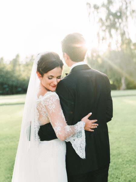 Bride with long flared sleeves and stylish black tie Groom embrace happily on lawn at Sølyst Copenhagen