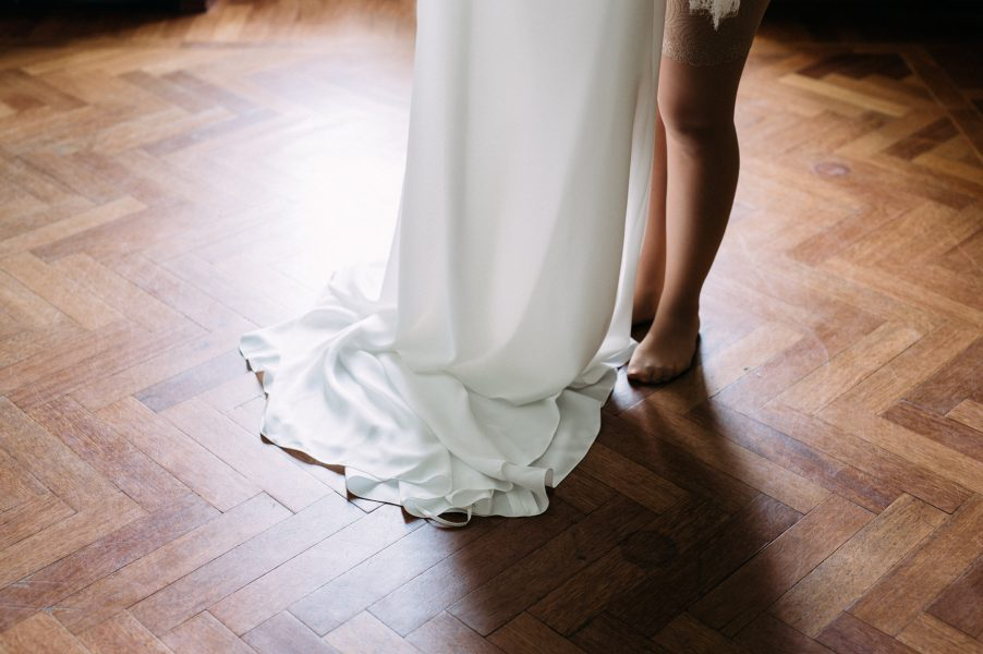 Bride about to step into wedding dress draped on parquet floor Sølyst Copenhagen København