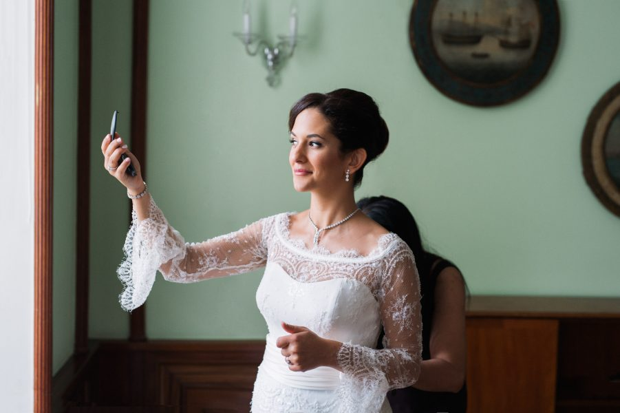 Bride holding up make up mirror in a scallop sleeved wedding dress Sølyst Copenhagen København