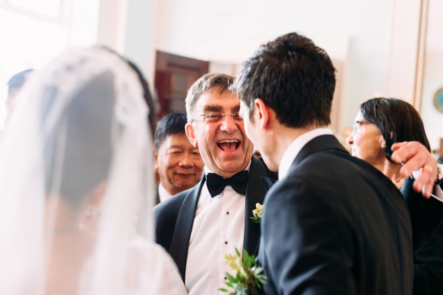 Wedding guest congratulates Groom with smiling great energy Sølyst Copenhagen