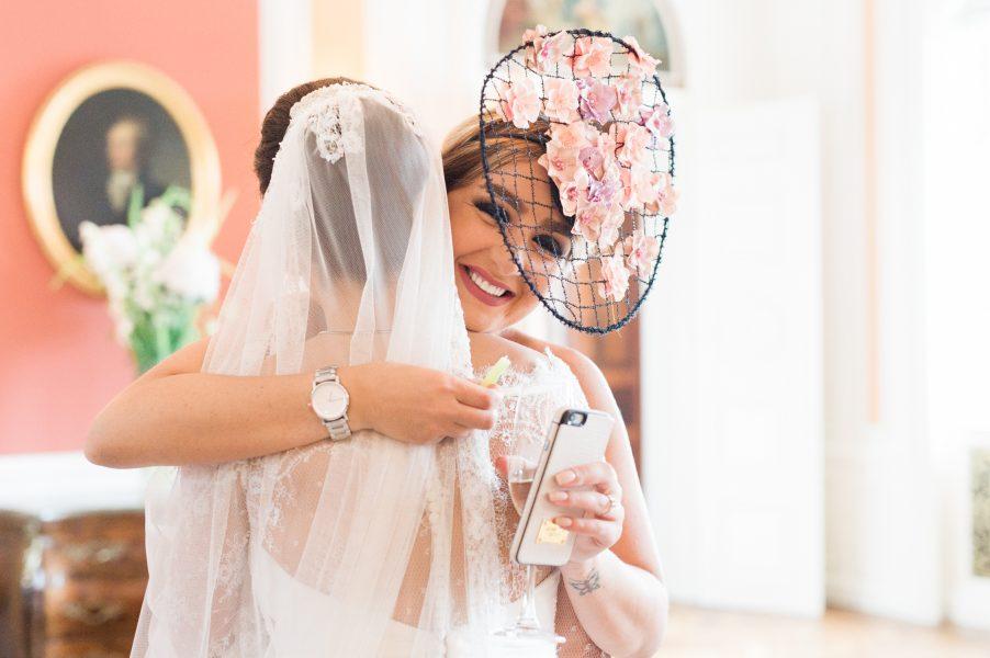 Glamorous guest in pink floral fascinator hugs bride Sølyst Copenhagen
