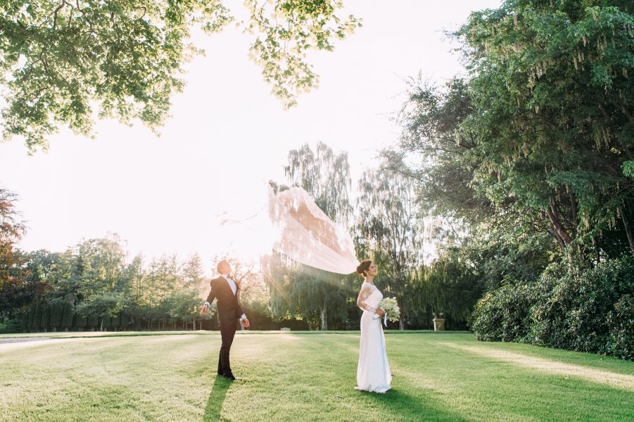 Fine Art portrait of Groom towing Bride's veil in the air on the lawn at Sølyst Copenhagen
