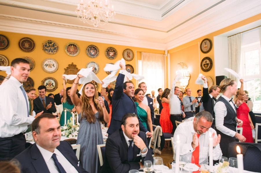 Guests cheer and wave napkins over heads as Bride and Groom enter wedding breakfast room Sølyst Copenhagen
