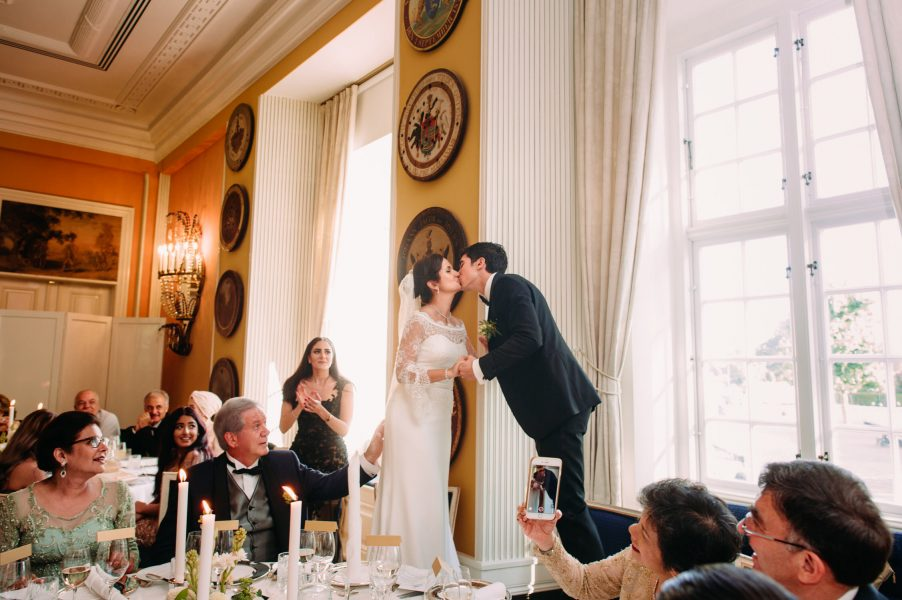 Bride and Groom kiss standing on chair during wedding reception Danish tradition Sølyst Copenhagen