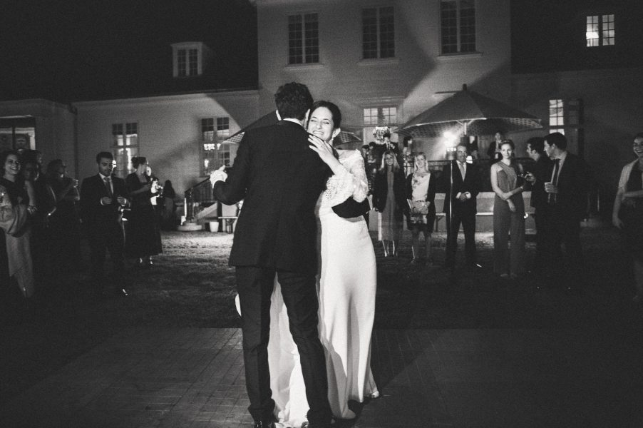 Classic black and white photo of Bride and Groom doing their first dance outside in the grounds of Solyst Copenhagen surrounds by torches