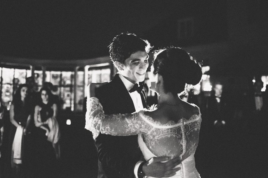 Classic black and white photo Groom having romantically at Bride whilst doing their first dance outside in the grounds of Solyst Copenhagen surrounds by torches